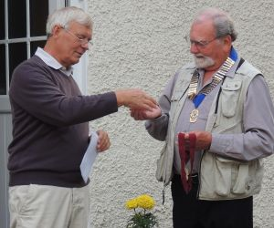 Lion Ken Carter (left) hands over the chain of office to Lion Brian Proctor